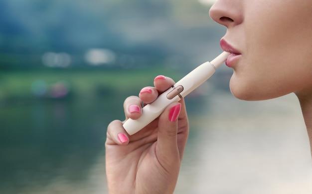 De volwassen vrouwelijke mening die van het gezichtsprofiel in openlucht elektronische sigaret roken Premium Foto