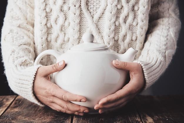 De volwassen vrouwenhanden omhelzen grote ceramische theepot met binnen warme drank. Gratis Foto
