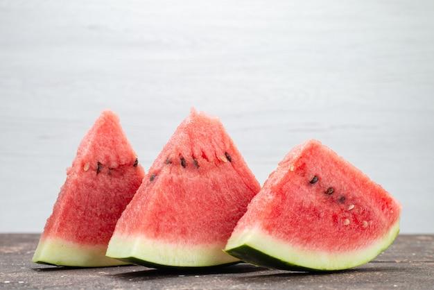 De vooraanzichtwatermeloen snijdt verse sappige en zachte vruchten op het sap van de grijze, fruitzomer Gratis Foto