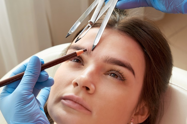 De vorm van de wenkbrauwen veranderen. stylist de wenkbrauwen meten met de liniaal. het proces van micropigmentatie in een schoonheidssalon. vrouw die haar wenkbrauwen heeft gekleurd met semi-permanente make-up. Premium Foto