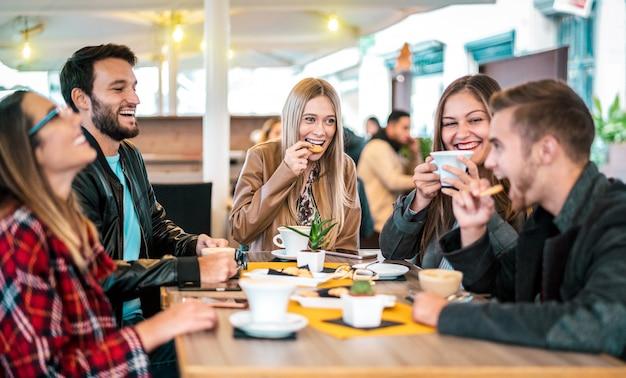 De vrienden groeperen het drinken cappuccino bij koffiebar Premium Foto