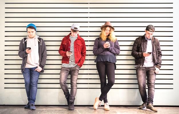 De vrienden groeperen het gebruiken van smartphone tegen muur bij de onderbreking van de universitaire universiteitsbinnenplaats Premium Foto