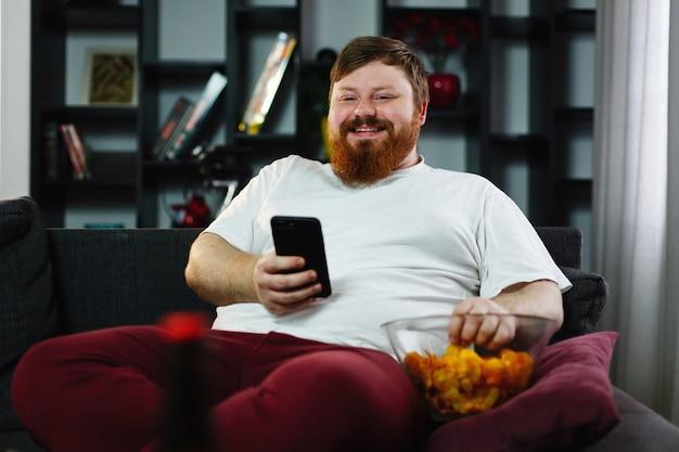 De vrij dikke mens glimlacht controlerend zijn smartphone terwijl hij op de bank zit en eet Gratis Foto