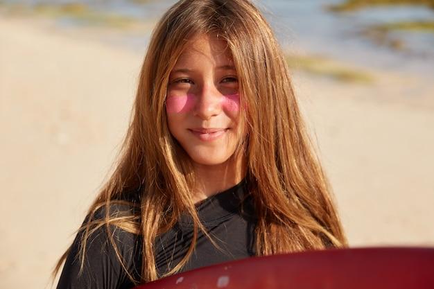De vrij jonge actieve vrouw met lang haar, heeft een roze beschermend masker om te surfen Gratis Foto