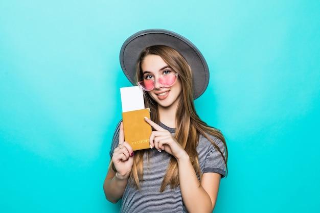 De vrij jonge tienerdame houdt haar paspoortdocumenten met kaartje in haar handen die op groene studiomuur worden geïsoleerd Gratis Foto