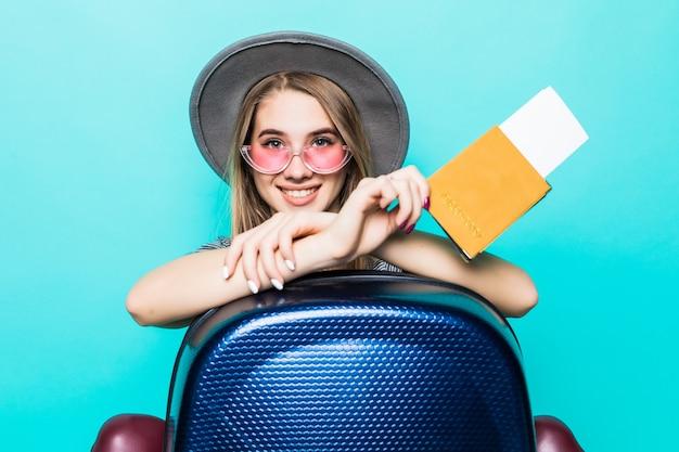 De vrij jonge tienerdame houdt haar paspoortdocumenten met kaartje in haar handen en blauwe koffer die op groene studiomuur wordt geïsoleerd Gratis Foto