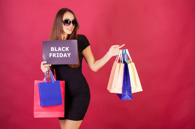 De vrij jonge vrouw kleedde zich stijlvol in zwarte met zakken na het winkelen op zwarte vrijdag Premium Foto