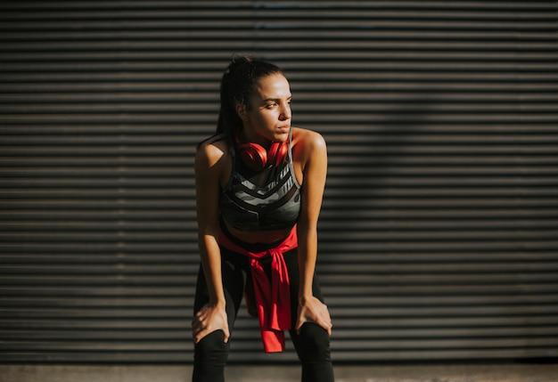 De vrij jonge vrouw neemt een pauze na het lopen in stedelijk gebied Premium Foto