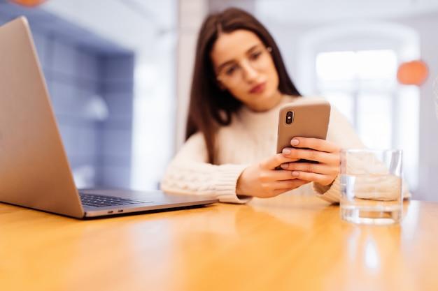 De vrij jonge vrouw zit op de keuken met laptop die videocall op haar telefoon heeft Gratis Foto