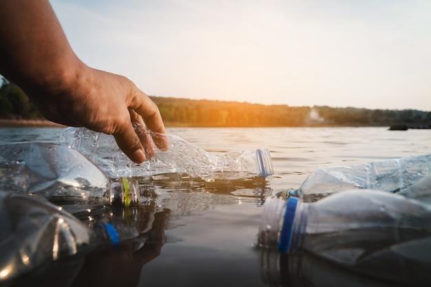 De vrijwilliger haalt een plastic flesje in de rivier op en beschermt het milieu tegen een vervuilingsconcept. Premium Foto