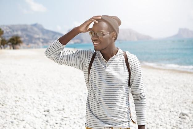 De vrolijke afrikaanse jonge mens die zich op strand bevinden en met verrukkelijke glimlach opzij kijken, merkte zijn vriend op die hoofd raakt. zomervakanties en avonturen. mensen, levensstijl en reizen Gratis Foto