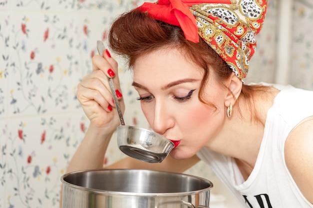 De vrolijke huisvrouw in een rode hoofddoek in de keuken probeert de soep Premium Foto