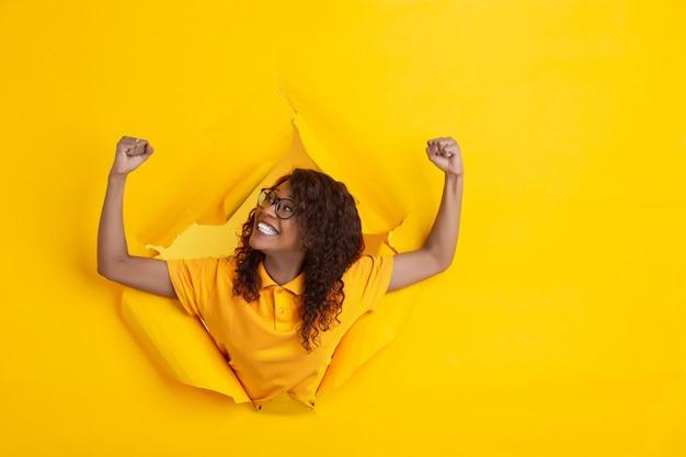 De vrolijke jonge vrouw stelt op gescheurde gele document gatenachtergrond, emotioneel en expressief Gratis Foto