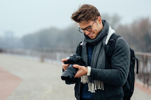 De vrolijke knappe mens in oogglazen bekijkt foto's in de camera. Gratis Foto