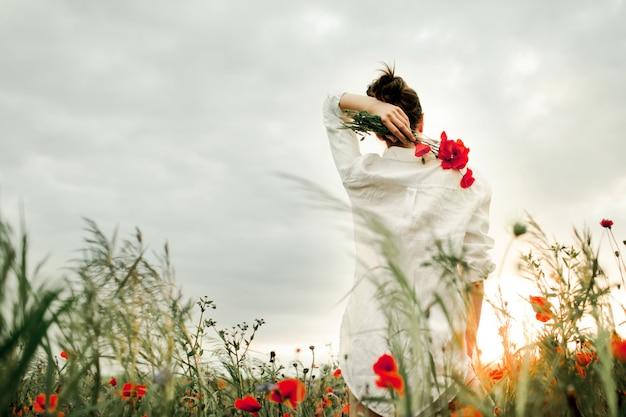 De vrouw bevindt zich houdend een boeket van de papaversbloem over een rug, onder de weide Gratis Foto