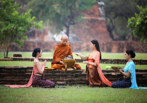 De vrouw bidt de monnik met voedsel bij openlucht Premium Foto