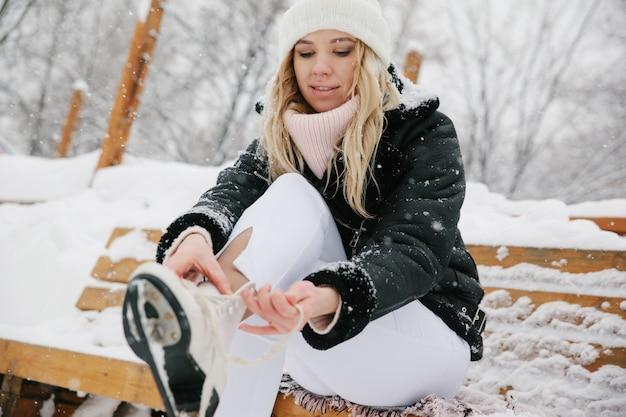 De vrouw bindt schoenveters bij kunstschaatsen bij ijsbaan. detailopname Premium Foto