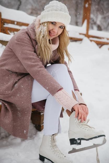 De vrouw bindt schoenveters bij kunstschaatsen bij ijsbaan. Premium Foto