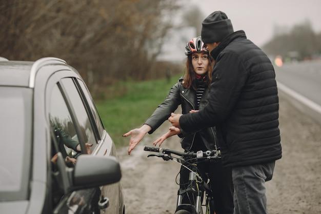 De vrouw botste tegen de auto. meisje in een helm. mensen maken ruzie over het ongeluk. Gratis Foto