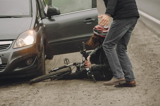 De vrouw botste tegen de auto. meisje in een helm. Gratis Foto