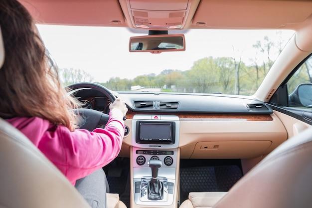 De vrouw die de moderne auto op de asfaltweg naar de zonsondergang drijft Premium Foto
