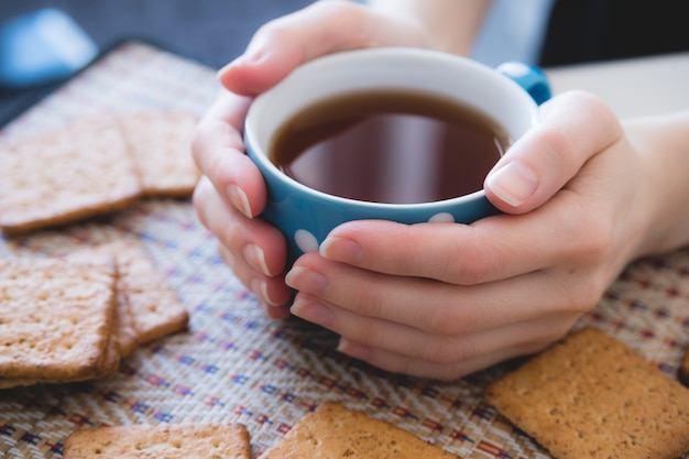 De vrouw die een kop van hete thee of koffie houdt, ligt naast koekjes, close-up Premium Foto