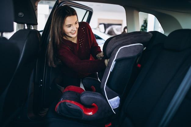 De vrouw die een veiligheidsauto installeert zit in een auto Gratis Foto
