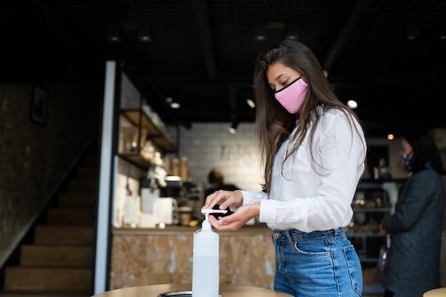 De vrouw die ontsmettingsmiddelgel gebruikt maakt handen schoon bij koffie. Gratis Foto