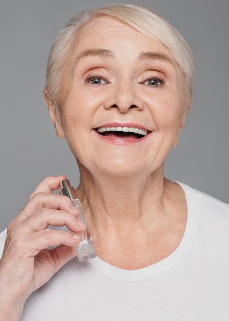 De vrouw die van de close-upsmiley parfum gebruikt Gratis Foto