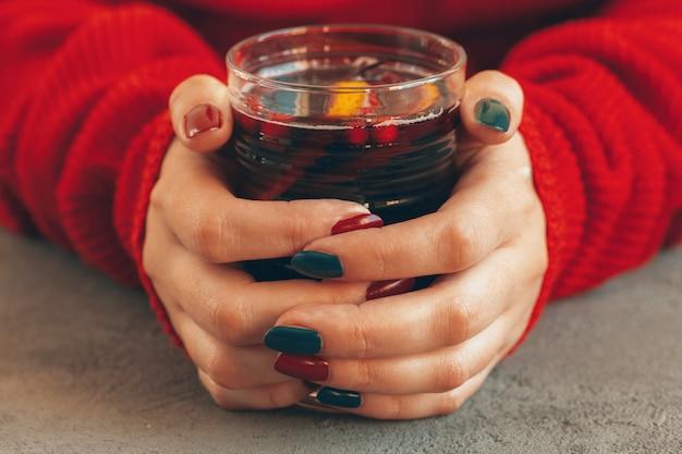 De vrouw dient warme sweater in houdend een kop glühwein Premium Foto