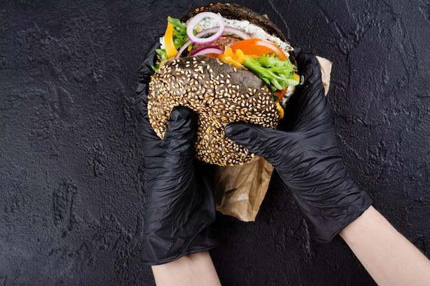 De vrouw dient zwarte rubberhandschoenen in houden sappige zwarte broodjeshamburger Premium Foto