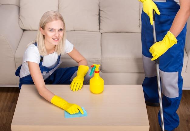 De vrouw doet wat schoonmaakwerk in het huis. Premium Foto