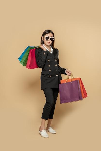 De vrouw draagt donkere kleding en een bril, samen met veel tassen, om boodschappen te doen Gratis Foto