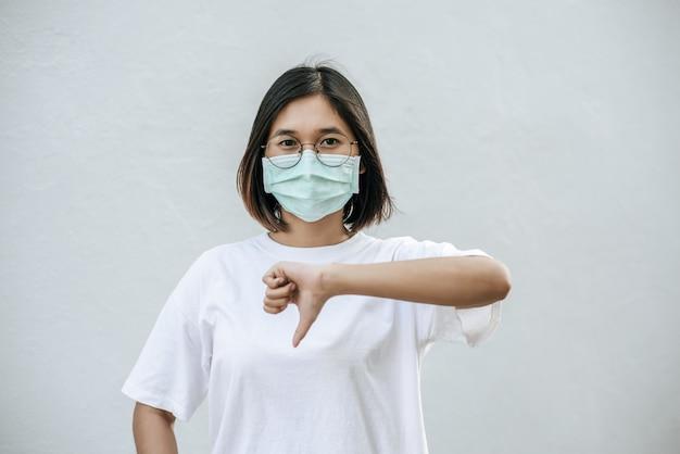 De vrouw draagt een masker en wijst met haar duim naar beneden. Gratis Foto