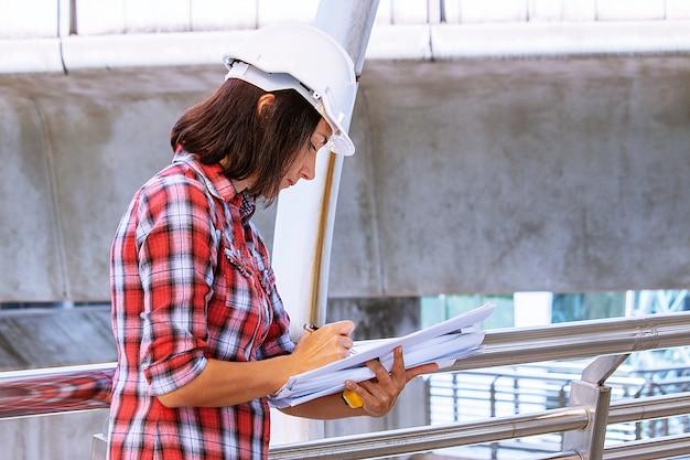 De vrouw draagt witte veiligheidshoed werkt bij bouwwerf Premium Foto