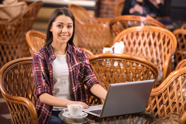 De vrouw drinkt koffie en gebruikt laptop in een koffiewinkel. Premium Foto
