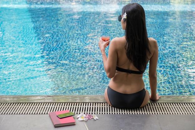 De vrouw drinkt sap dichtbij pool bij de zomer Premium Foto