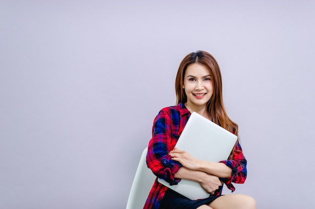 De vrouw en de telefoon met wit scherm plaatsen de ruimte en hebben een computer altijd klaar om te werken. Premium Foto