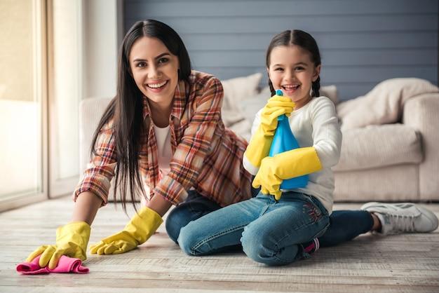 De vrouw en haar dochter glimlachen terwijl het schoonmaken van vloer. Premium Foto