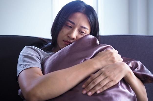De vrouw ging zitten en omhelsde het kussen op de bank in huis. de uitdrukking en wanhoop en wanhoop. Premium Foto