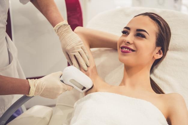 De vrouw glimlacht terwijl de arts laserepilatie doet. Premium Foto