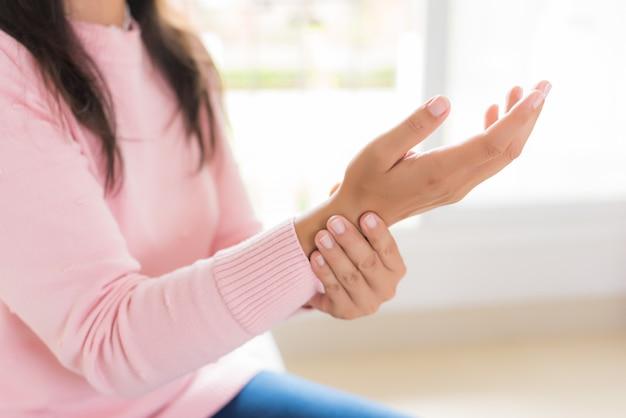 De vrouw houdt de verwonding van de polshand en het voelen van pijn, gezondheidsconcept. Premium Foto