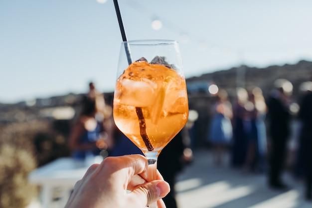 De vrouw houdt een glas met oranje drank met ijsblokjes tegen de zon Gratis Foto