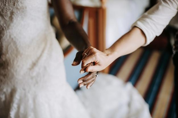 De vrouw houdt hand van afrikaanse amerikaanse bruid Gratis Foto