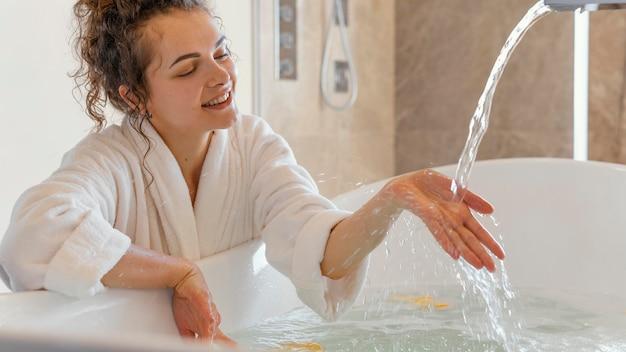 De vrouw in badjas met dient water in Gratis Foto