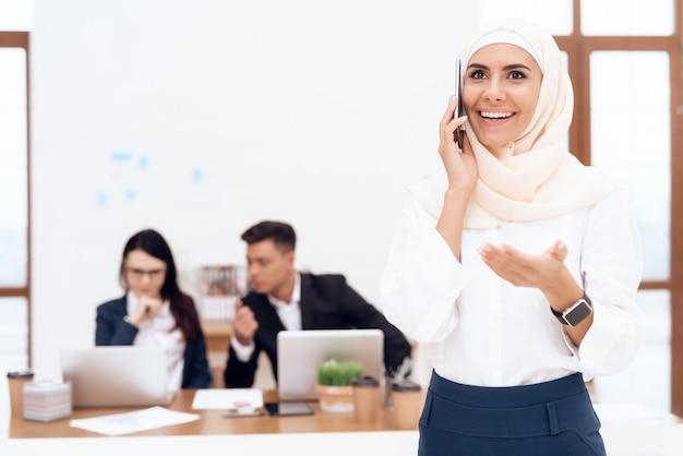 De vrouw in de hijab staat in het callcenter Premium Foto