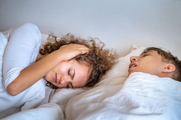 De vrouw is geïrriteerd door haar man die snurkt. Premium Foto