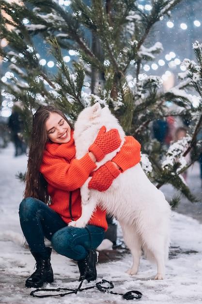 De vrouw koestert haar hond op een nachtstraat Gratis Foto