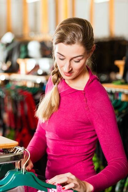 De vrouw koopt tracht of dirndl in een winkel Premium Foto