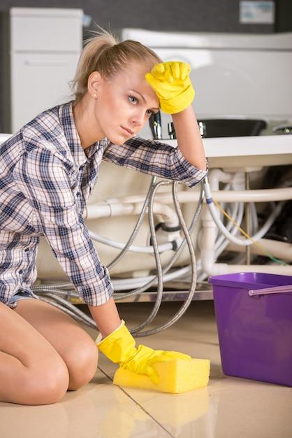 De vrouw maakt de vloer met emmer water schoon. Premium Foto
